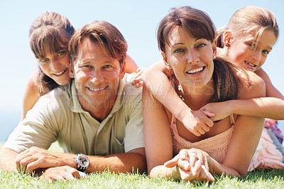 Buy stock photo Portrait of family lying together on grass and smiling