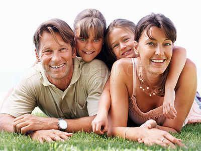 Buy stock photo Portrait of smiling family lying together on grass