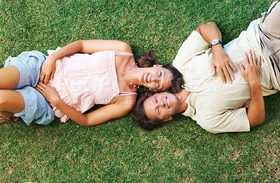 Buy stock photo Top view of couple lying on grass with heads together