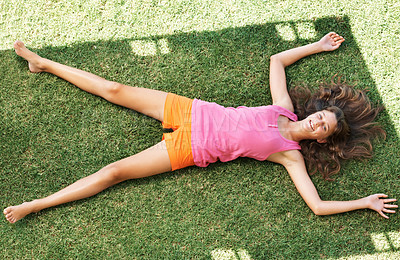 Buy stock photo Top view of cute girl relaxing on grass and smiling