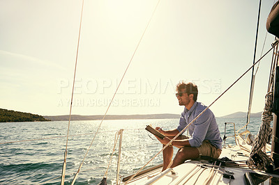 Buy stock photo Shot of a young man writing while out on his yacht