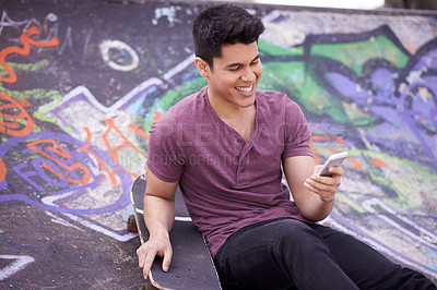 Buy stock photo Shot of a young skateboarder using his phone at a skatepark