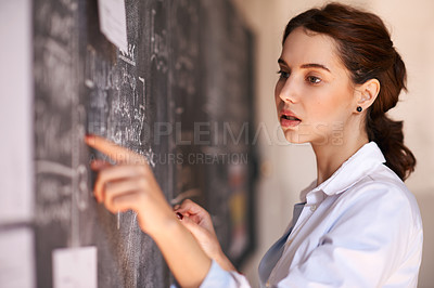 Buy stock photo Cropped shot of a young teacher working on her chalkboard