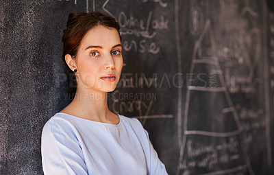 Buy stock photo Cropped portrait of a young teacher leaning against her chalkboard
