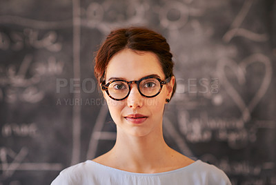 Buy stock photo Cropped portrait of a young teacher standing in front of a chalkboard in her classroom