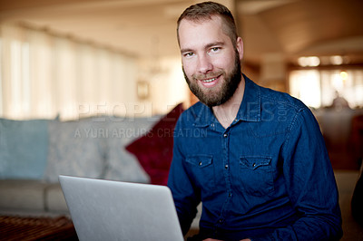 Buy stock photo Cropped portrait of a young man using his laptop while sitting on a sofa at home