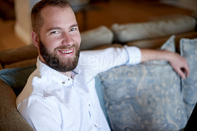 Buy stock photo Cropped portrait of a young man sitting on the sofa at home