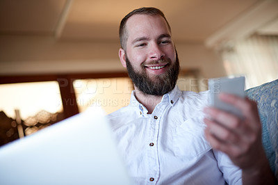 Buy stock photo Shot of a young man using a phone and laptop on the sofa at home