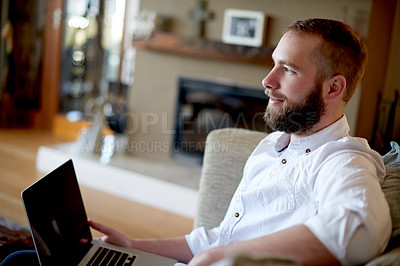 Buy stock photo Shot of a young man using a laptop on the sofa at home
