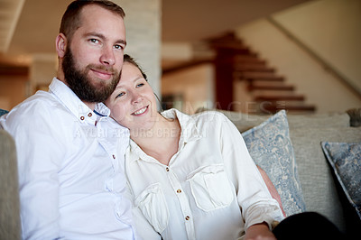 Buy stock photo Portrait of a young couple relaxing on the sofa at home