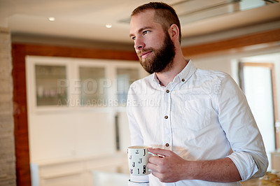 Buy stock photo Shot of a young man having a beverage at home
