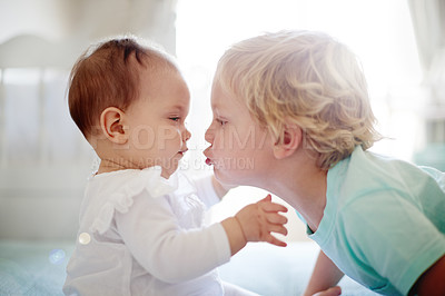 Buy stock photo Shot of a young boy kissing his baby sister
