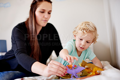 Buy stock photo Shot of a mother sitting with her little boy while he's playing with his toys