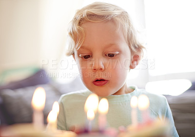 Buy stock photo Shot of a little boy about to blow out the candles on his birthday cake