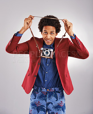 Buy stock photo Shot of a young man hanging his camera around his neck against a gray background