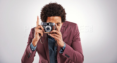 Buy stock photo Shot of a young man holding a camera against a gray background