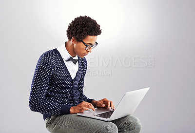 Buy stock photo Studio shot of a young man reading the newspaper against a gray background