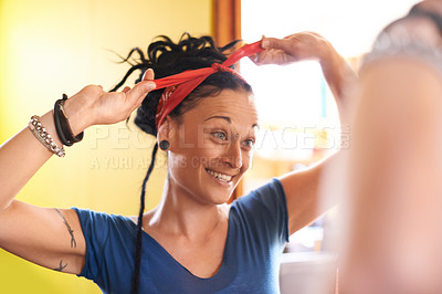 Buy stock photo Shot of an attractive woman with dreadlocks tying up her hair in front of the mirror