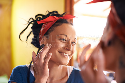 Buy stock photo Shot of an attractive woman with dreadlocks examining herself in the mirror