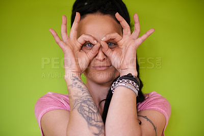 Buy stock photo Shot of an attractive young woman with dreadlocks peeking through her fingers  against a green background