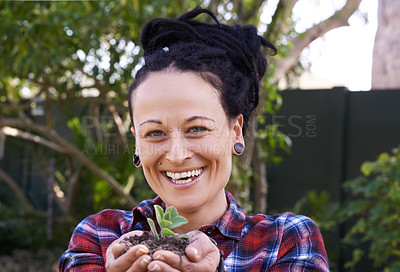 Buy stock photo Shot of a woman holding a handful of soil with a budding plant