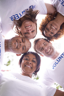 Buy stock photo Low angle shot of a group of volunteer workers standing in a huddle outside