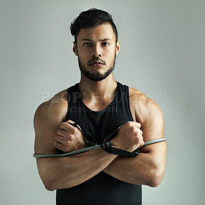 Buy stock photo Studio shot of a young man working out with a resistance band against a gray background