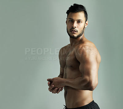 Buy stock photo Studio shot of an athletic young man flexing his muscles against a gray background