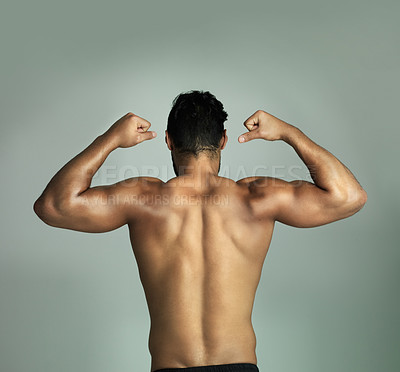 Buy stock photo Rearview shot of an athletic young man flexing his muscles against a gray background
