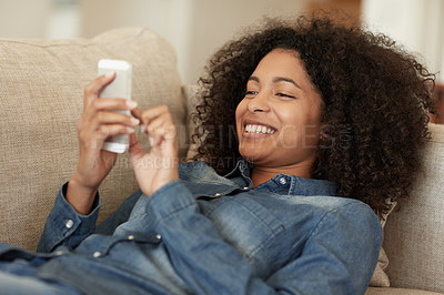 Buy stock photo Shot of a young woman using her phone on the sofa at home