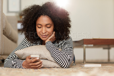 Buy stock photo Shot of a young woman relaxing on the floor with her mobile phone at home