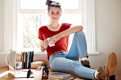 Buy stock photo Shot of a teenage girl drinking a cup of coffee while relaxing at home