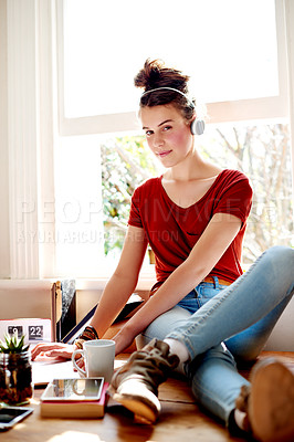 Buy stock photo Shot of a teenage girl listening to music while using her laptop