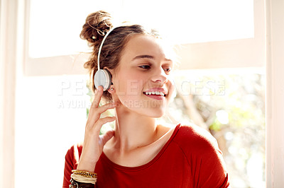 Buy stock photo Shot of a teenage girl listening to music while relaxing at home