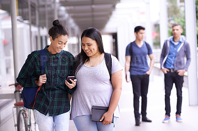 Buy stock photo Shot of two university students reading a text message on campus