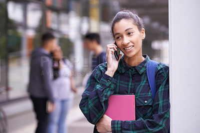 Buy stock photo Shot of a university student talking on her phone while standing on campus