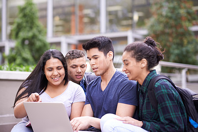 Buy stock photo Shot of a group of university students using a laptop while sitting on some steps on campus