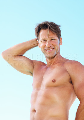 Buy stock photo Portrait of smart muscular man standing against sky with hand behind head and smiling
