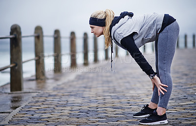 Buy stock photo Shot of a young woman catching her breath after a run