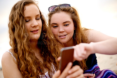 Buy stock photo Shot of girlfriends using a mobile phone together outdoors