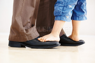 Buy stock photo Closeup of a little boy's feet standing on the tops of his dad's shoes - copyspace