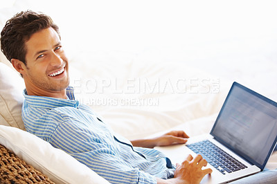 Buy stock photo Portrait of man sitting on a sofa using laptop and smiling