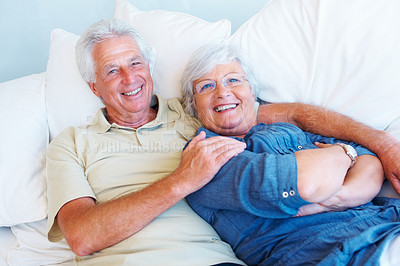 Buy stock photo Portrait of senior couple relaxing together on a sofa and smiling