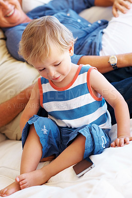 Buy stock photo Little kid sitting on sofa with grandparents and looking at the mobile phone