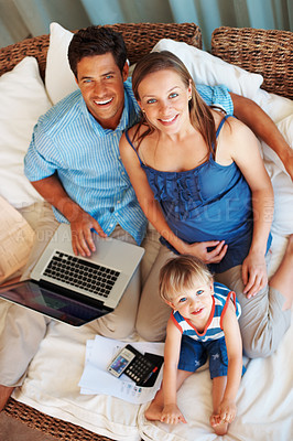 Buy stock photo High angle view of a happy family smiling up at you while sitting on a sofa using a laptop and calculator