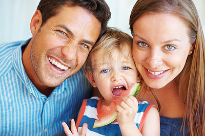 Buy stock photo Closeup portrait of couple smiling with kid eating watermelon
