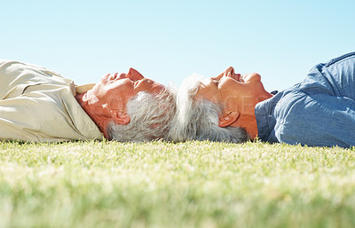 Buy stock photo Closeup of senior couple lying on the grass with heads together