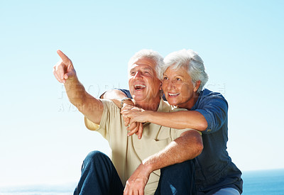 Buy stock photo Senior couple with man pointing away and woman embracing man from behind