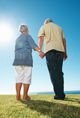 Buy stock photo Rear view of senior couple holding hands and standing together on grass