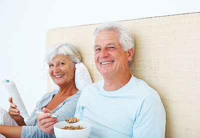 Buy stock photo Portrait of senior couple sitting on bed and smiling with man having breakfast and woman reading a novel